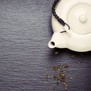 Pouso da Torre - Asia food composition with chinese chopsticks, teapot and dry green tea on a dark stone background, top view, toned, with free space for text